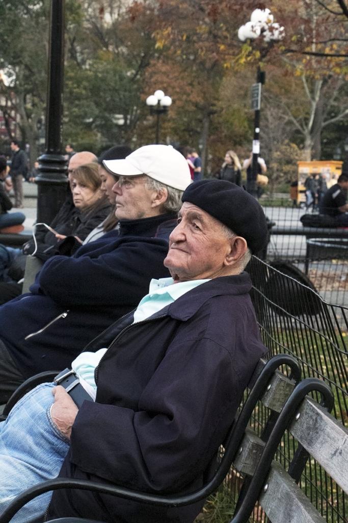 Homme agé assis sur un. banc du Washnigton Square Park