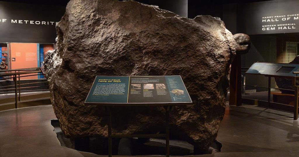 Météorite avec un panneau d'explication devant dans le musée d'histoire naturelle.