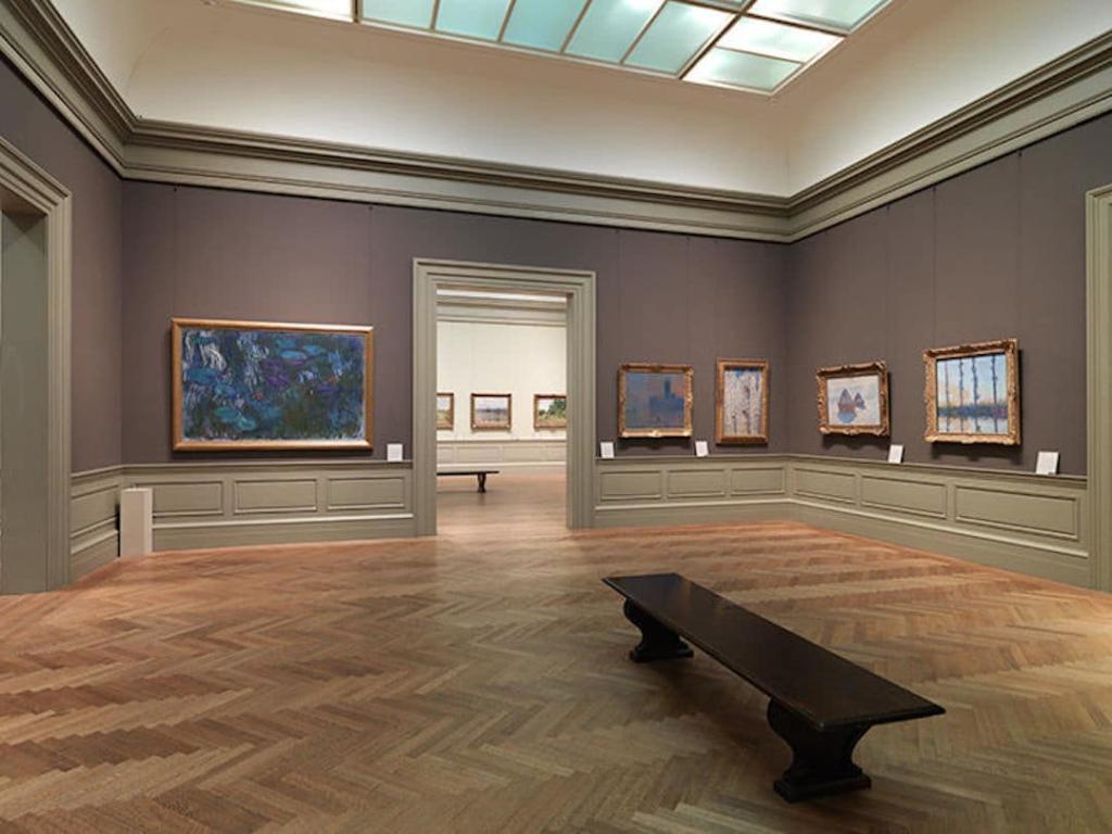 Salle de musée MET avec des tableaux accrochés au mur.