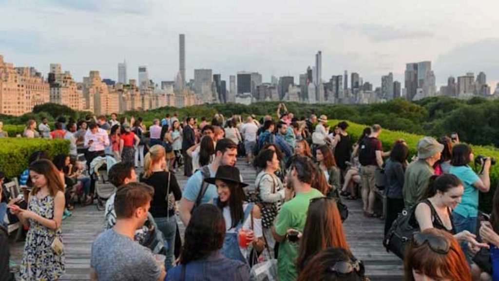 Extérieur d'un Rooftop rempli de personnes qui parlent, avec vu sur la Skyline de New York.