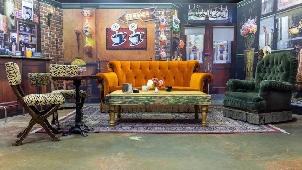 Canapé orange au centre et des fauteuils de chaque côté dans le café Central Perk à New York