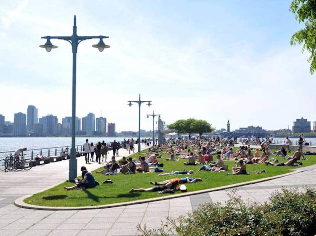 Vue sur le Hudson River Park, avec de nombreuses personnes assises sur l'herbe face à la rivière.