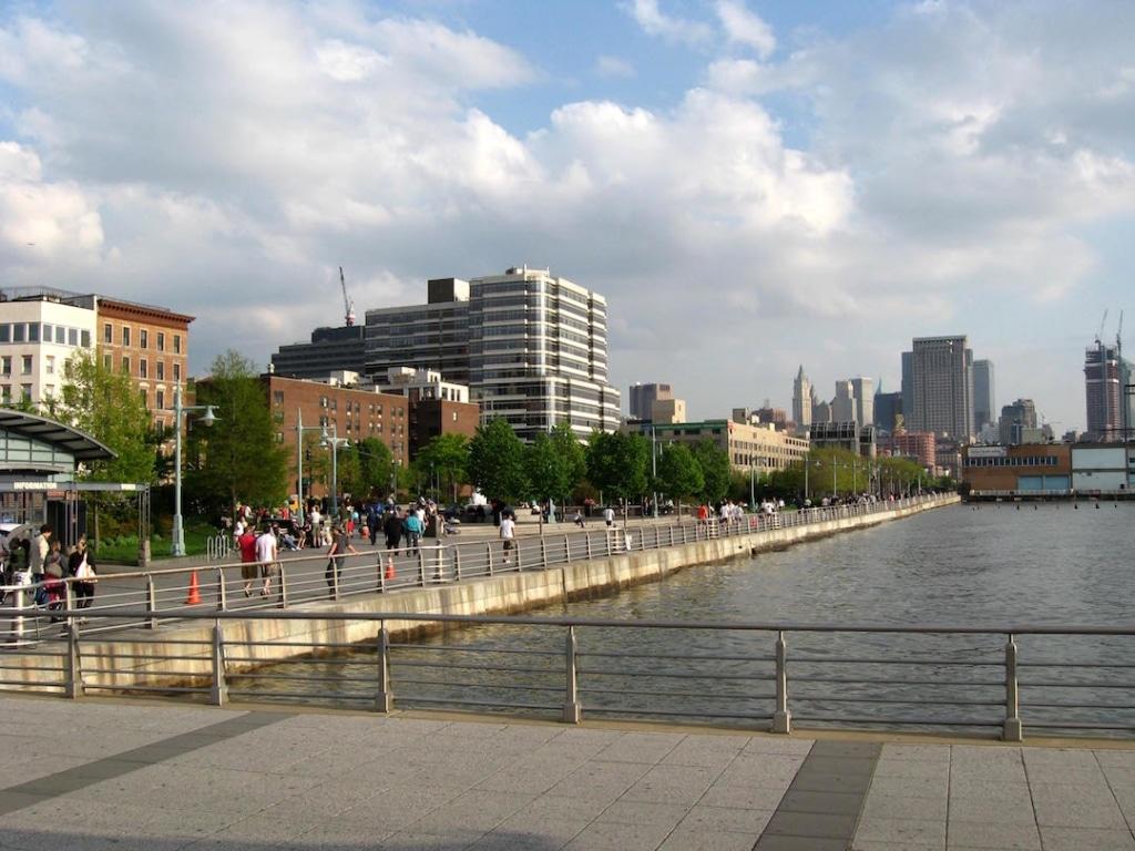 Vue sur le Hudson River Park. Il y a des personnes qui marchent le long de la rivière et des buildings à l'arrière plan.