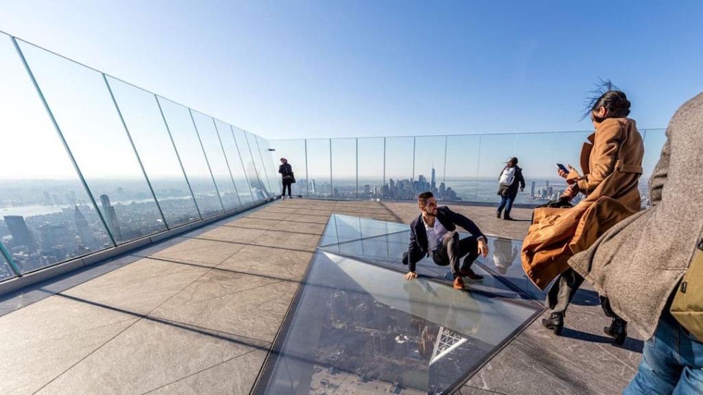 Homme se faisant prendre en photo sur une plateforme en verre en haut de l'observatoire The Edge.