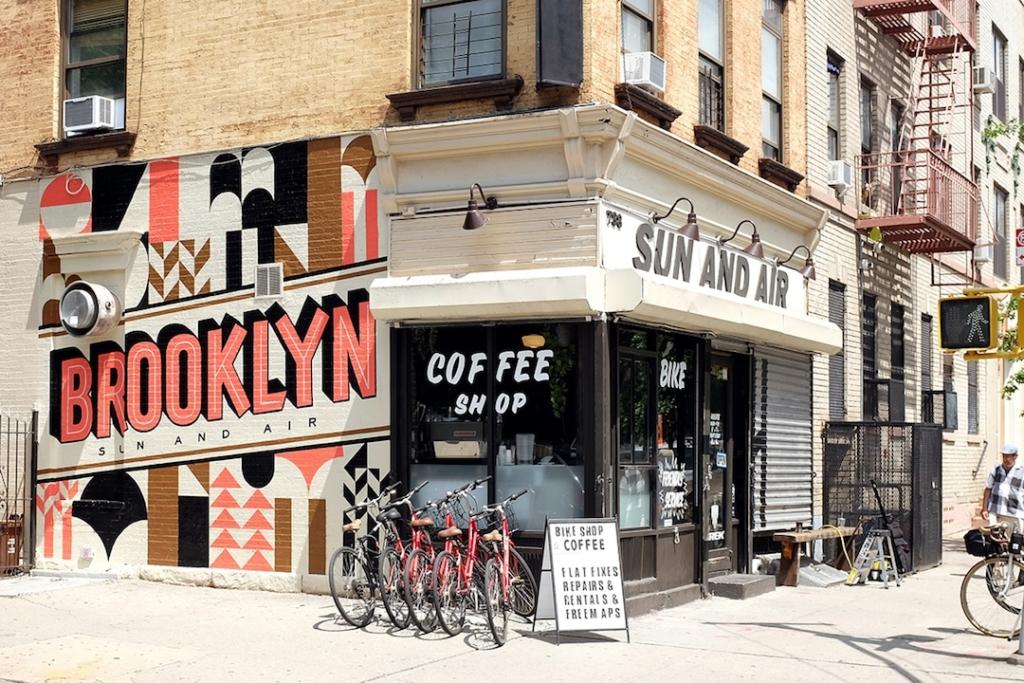 Extérieur du magasin Sun and Air à New York avec du street art sur le mur : Brooklyn écrit en gros.