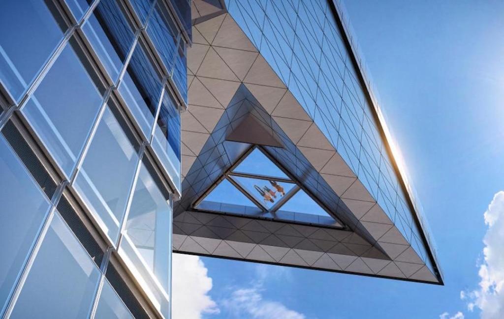 Vue d'en dessous de la plateforme extérieure de The Edge. On voit des personnes allongées sur la partie en verre de la plateforme.