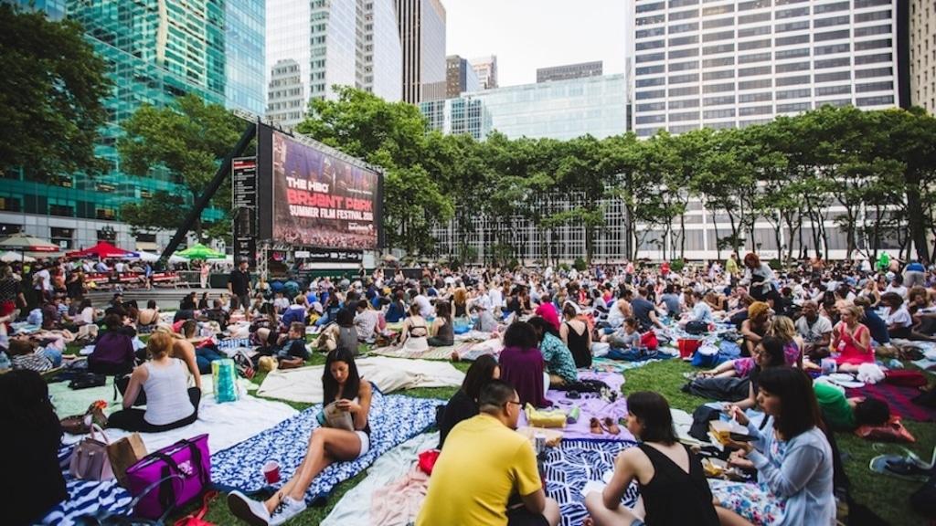 New yorkais assis sur la pelouse du Bryant Park prêt à regarder un film en plein air.