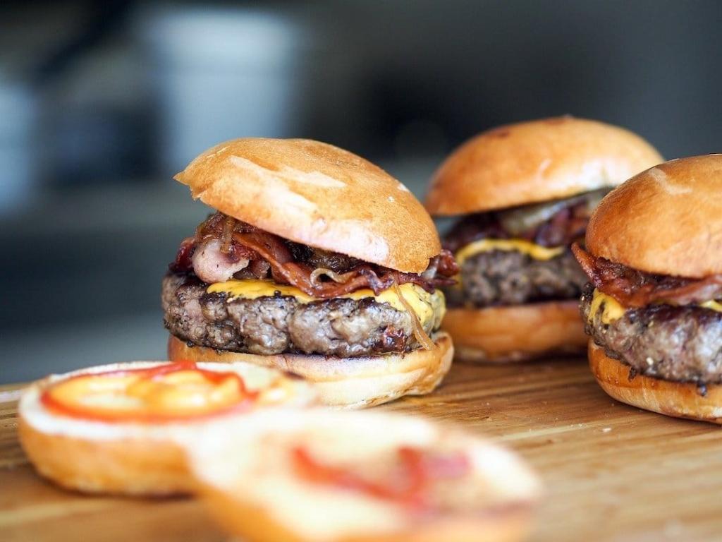 3 burgers sur une table avec des pains ouverts à l'avant