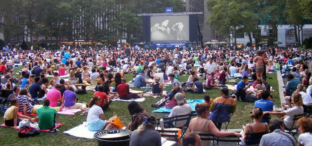 Personnes installées sur une pelouse regardant un film.