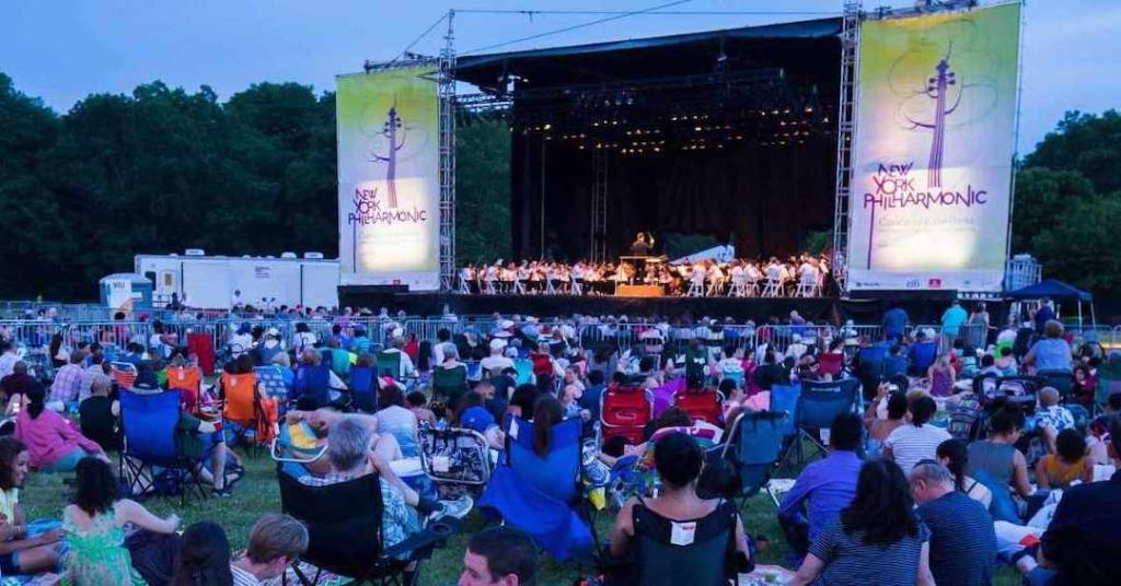 Personnes assises sur une pelouse en train de regarder un concert d'orchestre.