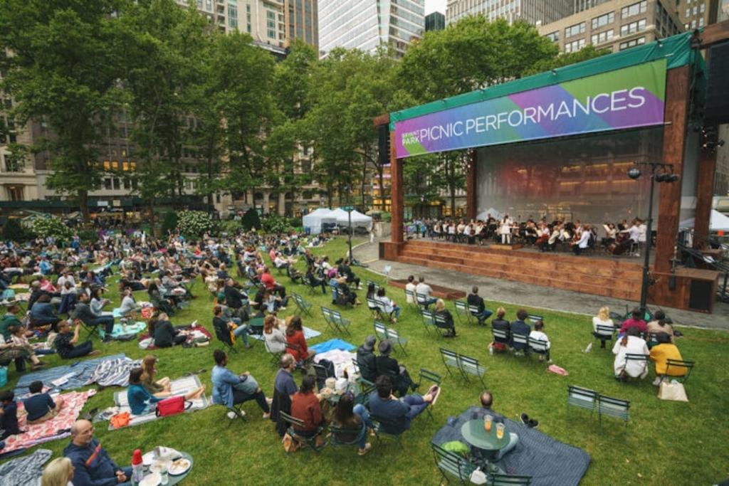 Personnes assises sur la pelouse de Bryant Park regardant un spectacle durant un Picnic Performances.
