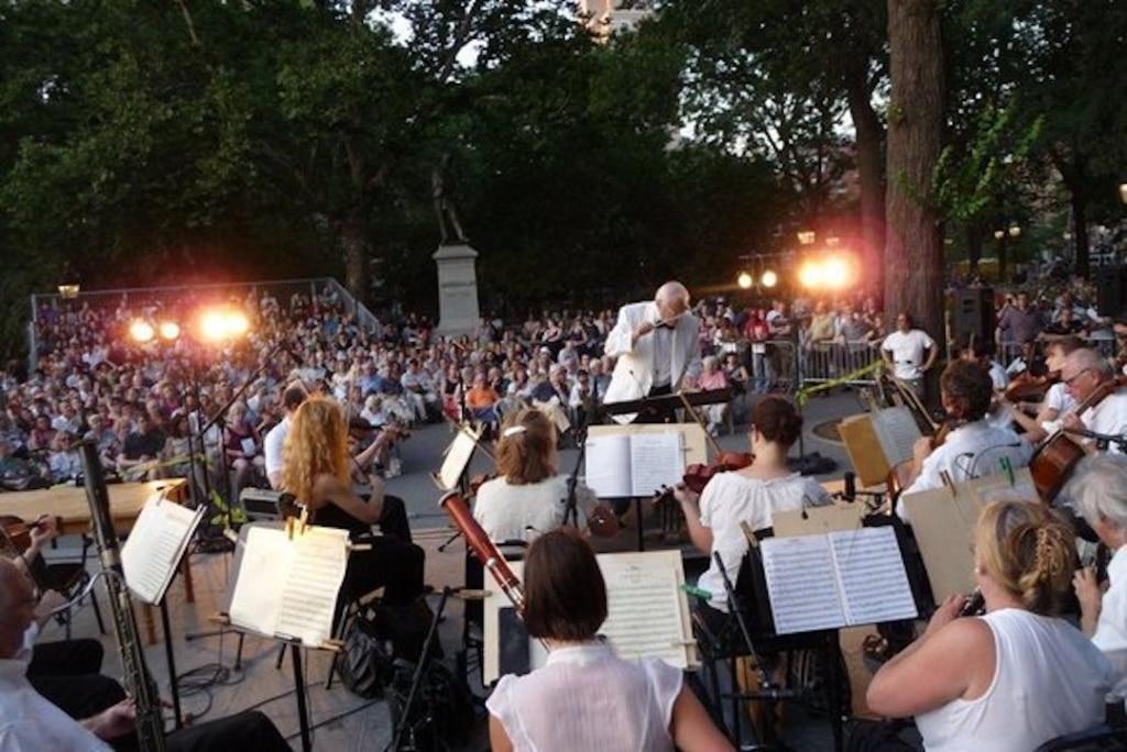 Musiciens pendant un concert au Washington Square Park entourés de spectateurs.