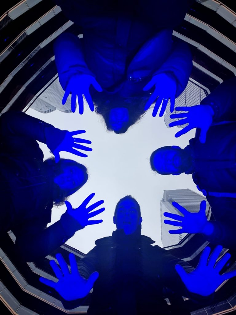 4 personnes vus d'en bas avec lumière bleue sur eux à The Vessel à New York