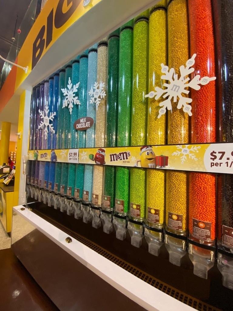 Tubes remplis de M&Ms triés par couleurs : oranges, jaunes, verts...